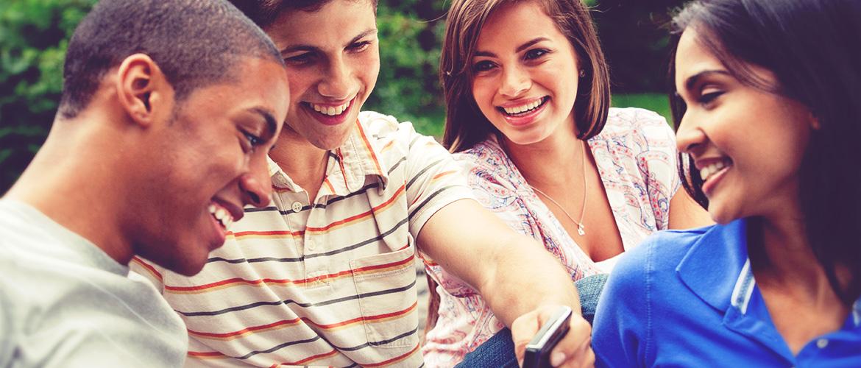 Un groupe d'adolescents regarde quelque chose de drôle sur un téléphone cellulaire