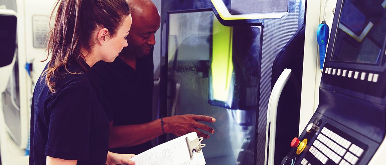 Un enseignant et une élève observant une machine à imprimer 3D